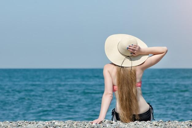 Hermosa chica en un sombrero y traje de baño se sienta en la playa. mar y cielo en la pared. vista desde atrás