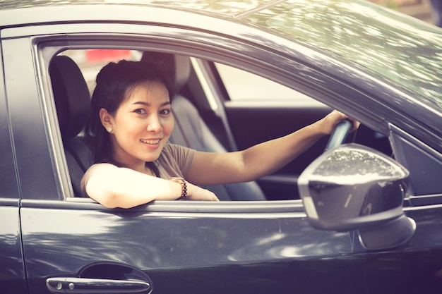 Hermosa chica sonríe mientras conduce un auto
