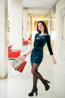 Hermosa chica sonriendo y haciendo compras en el centro comercial.