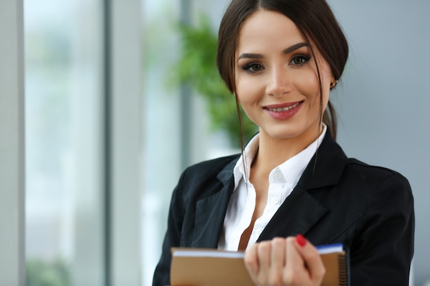 Hermosa chica sonriente empleado vistiendo traje sostenga cuaderno en el lugar de trabajo