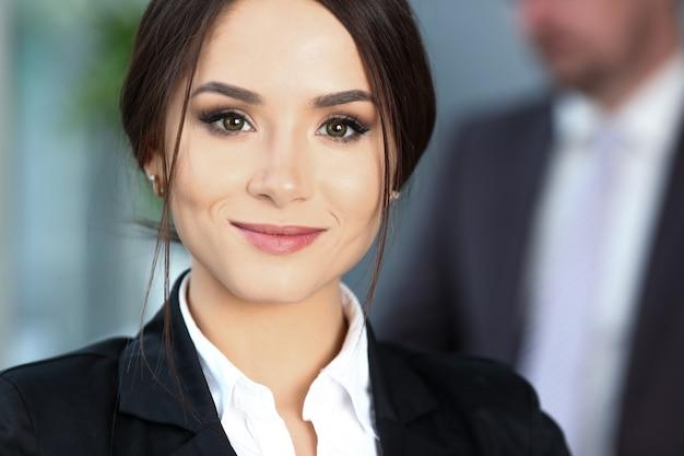 Hermosa chica sonriente empleado vistiendo traje sostenga cuaderno