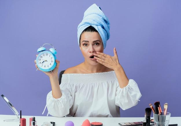 Hermosa chica sorprendida envuelta en toalla para el cabello se sienta en la mesa con herramientas de maquillaje sosteniendo el reloj despertador y pone la mano en la boca mirando aislado en la pared púrpura