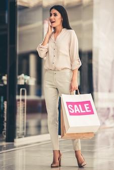 Hermosa chica está sosteniendo bolsas de compras