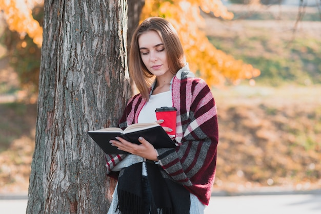 Hermosa chica sosteniendo un libro y una taza