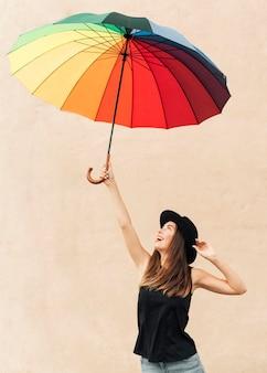 Hermosa chica sosteniendo un paraguas de arco iris