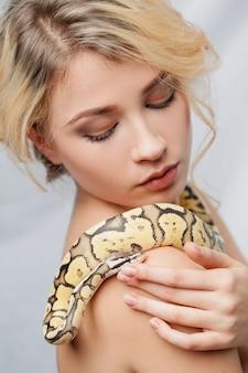Hermosa chica sosteniendo una pitón, que envuelve su cuerpo
