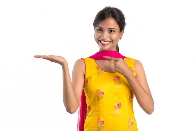 Hermosa chica sosteniendo y presentando algo en la mano con una sonrisa feliz.