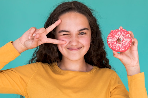 Hermosa chica sosteniendo una rosquilla glaseada