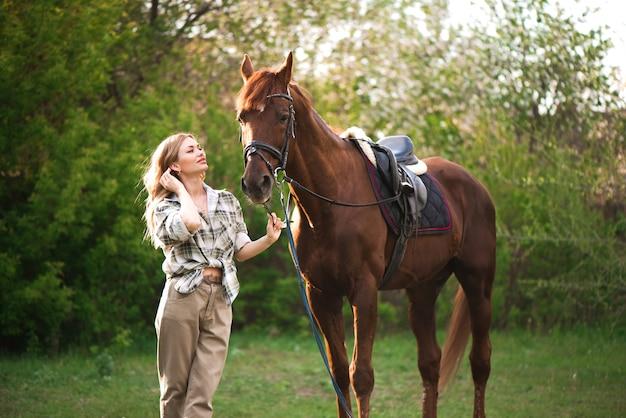 Hermosa chica con su caballo y hermoso atardecer cálido en el bosque de la primavera