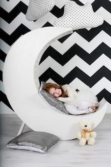 Hermosa chica en su habitación con la decoración de la luna y las nubes