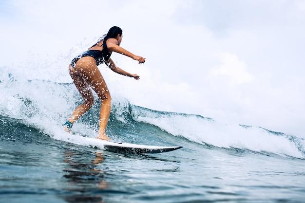 Hermosa chica surfista montando en un tablero