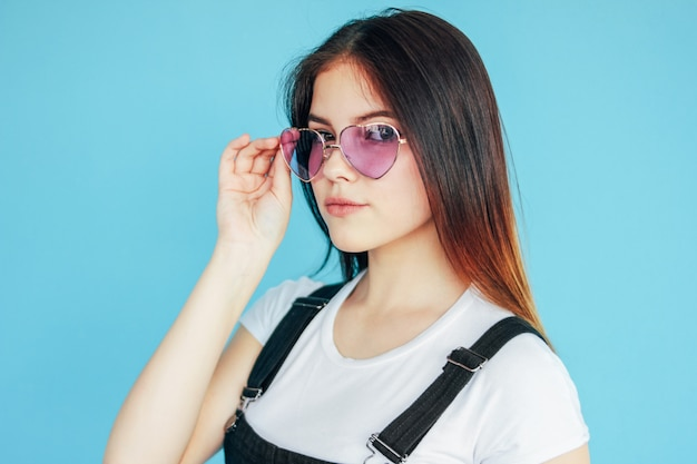 Hermosa chica surious en gafas de sol en forma de corazón con cabello largo oscuro en camiseta blanca aislada en azul