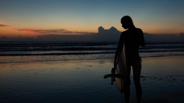 Hermosa chica con una tabla de surf al atardecer