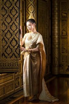 Hermosa chica tailandesa en traje nacional tailandés tradicional de pie junto a la ventana de una hermosa casa tailandesa dorada