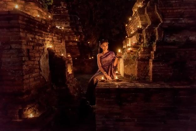Hermosa chica tailandesa en traje tradicional tailandés con vela en la noche