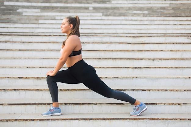 Hermosa chica de talla grande en top deportivo y leggings estirándose soñadoramente en las escaleras mientras pasa tiempo al aire libre