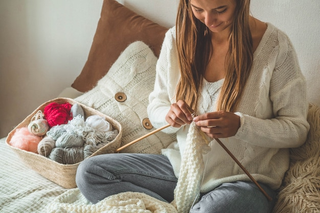 Hermosa chica teje un suéter caliente en la cama. tejer como hobby. accesorios para tejer.
