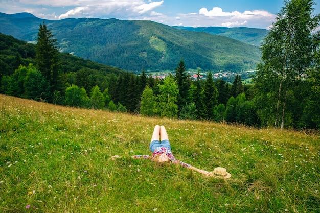 Hermosa chica tendida en la hierba en las montañas. increíble naturaleza de verano alrededor. concepto de armonía y pasión por los viajes. hipster viajando. mujer elegante disfrutando de la vida.