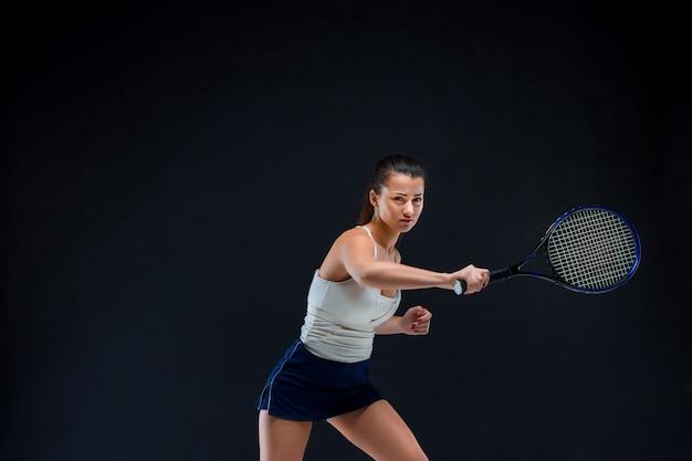 Hermosa chica tenista con una raqueta sobre fondo oscuro