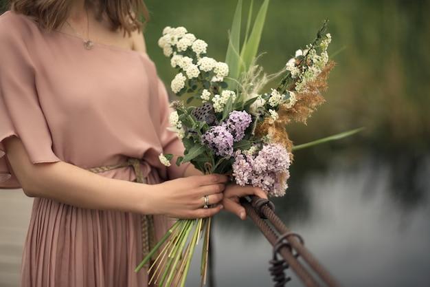 Hermosa chica tierna en un vestido color melocotón caminando sobre un puente de madera con un ramo de flores en las manos