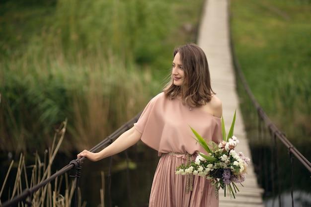 Hermosa chica tierna en un vestido color melocotón caminando sobre un puente de madera con un ramo de flores