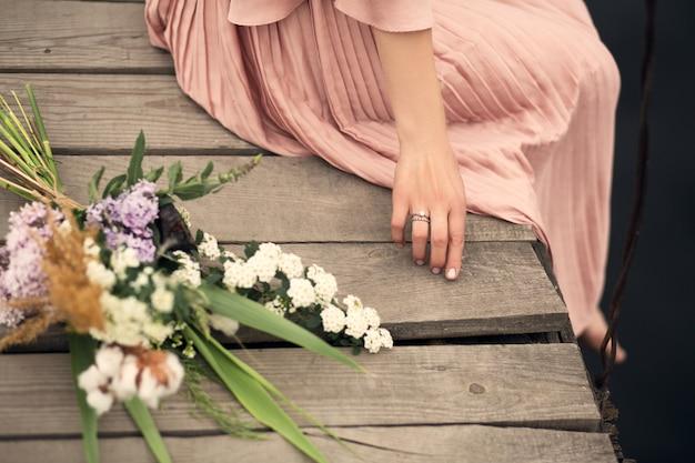 Hermosa chica tierna con un vestido color melocotón caminando sobre un puente de madera rural con un ramo de flores