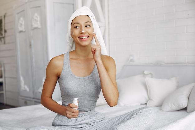 Hermosa chica con una toalla usando un producto de belleza