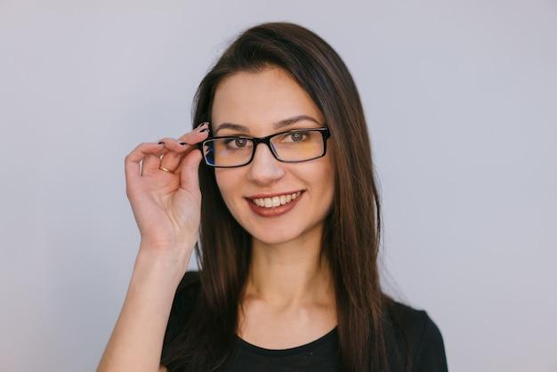 Hermosa chica toca un borde con gafas por los dedos y sonríe.