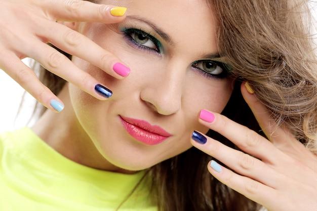 Hermosa chica toca su rostro con dedos de colores