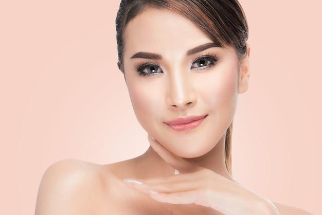 Hermosa chica tocando su rostro. perfeccione la piel fresca en fondo rosado con el camino de recortes.