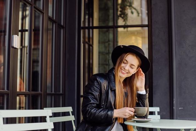 Hermosa chica tomando café en el café