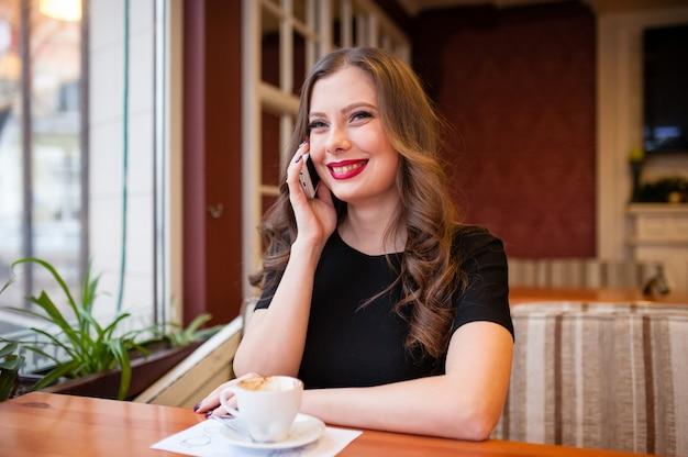 Hermosa chica tomando café y hablando por teléfono