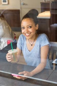 Hermosa chica tomando café en un restaurante