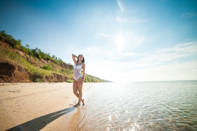 Hermosa chica tomando el sol y nadando en el mar