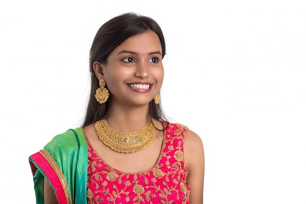 Hermosa chica tradicional india posando en superficie blanca.