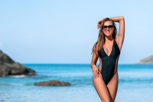 Hermosa chica en traje de baño negro y gafas de sol descansando cerca del océano en la playa.