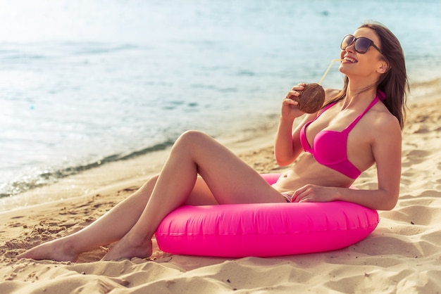 Hermosa chica en traje de baño rosa está bebiendo leche de coco.