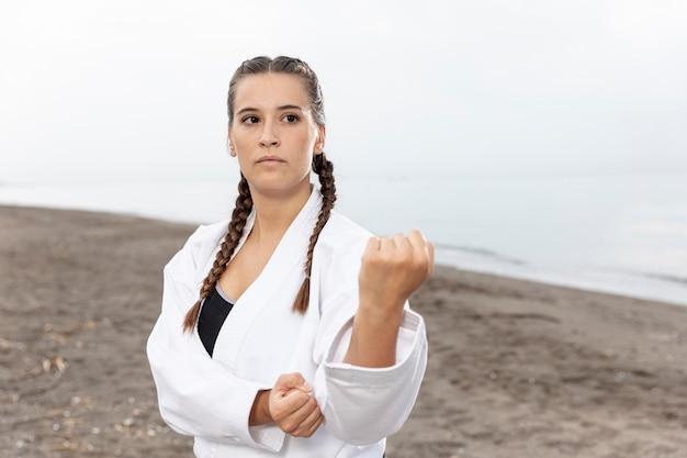 Hermosa chica en traje de karate al aire libre