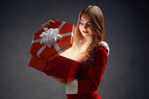 Hermosa chica en un traje rojo de snow maiden abre un regalo para año nuevo