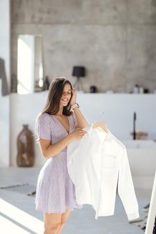Hermosa chica tratando de vestido en la habitación