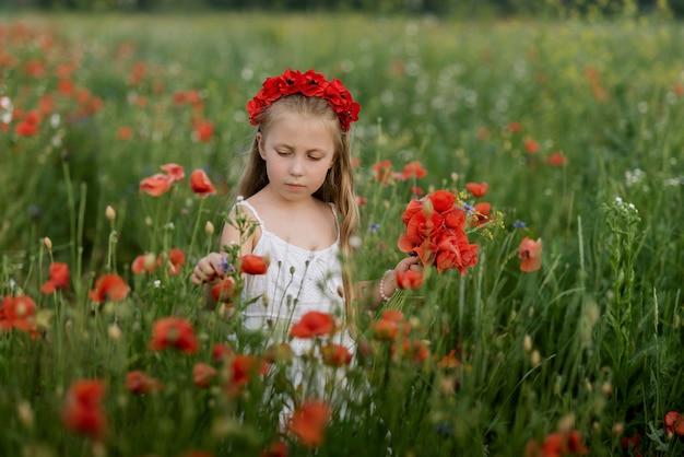 Hermosa chica ucraniana en campo de amapolas y trigo.