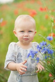 Hermosa chica ucraniana en vyshivanka con corona de flores en un campo de amapolas y trigo. . chica en bordado