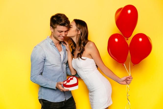 Hermosa chica vestida de blanco con globos rojos besando a su novio