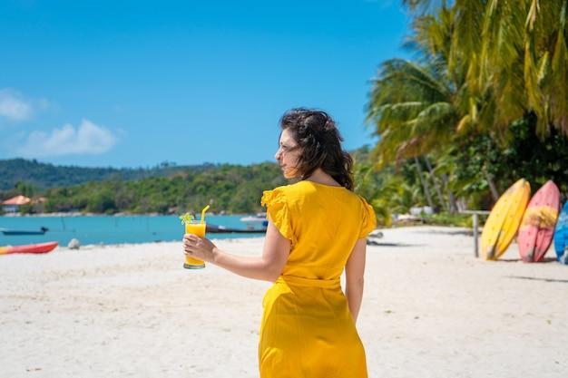 Hermosa chica en un vestido amarillo bebe mango fresco en la playa de una isla paradisíaca. vacaciones perfectas