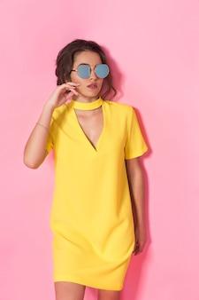 Hermosa chica en vestido amarillo con gafas de sol posando, sonriendo en espacio rosa en estudio