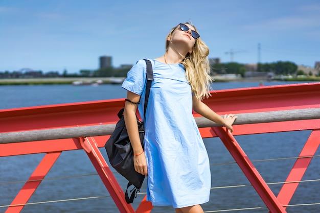 Hermosa chica en un vestido azul posando en el puente