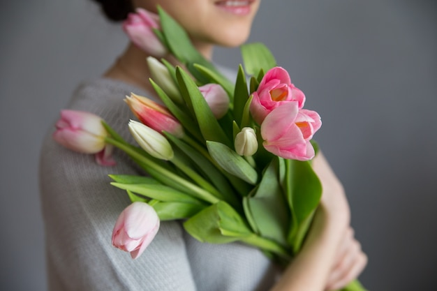 Hermosa chica en el vestido azul con tulipanes flores en manos sobre un fondo claro