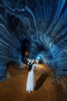 Hermosa chica en vestido blanco caminando en la cueva azul, tailandia