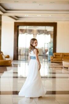 Hermosa chica con un vestido blanco en un hermoso interior.