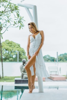 Hermosa chica en vestido blanco posando junto a la piscina